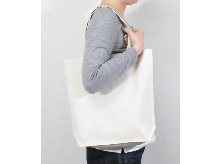 ライトキャンバスバッグ(生成)を肩に掛けているイメージ